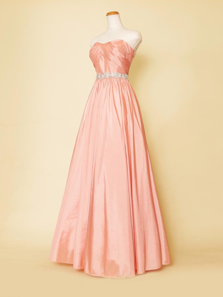 コーラルピンクカラーで肌色が美しく見えるウエストシルバーベルトのAラインロングドレス