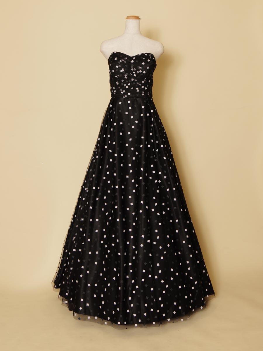 ブラックドレスにブロックパターンの白い模様をあしらったカジュアルテイストをプラスしたロングドレス