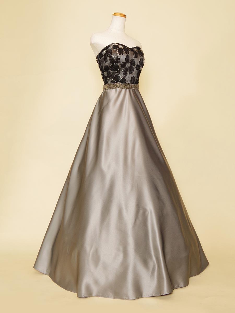 Aラインの滑らかスカートラインにブラックフラワーのマットな質感が美しく合わさったシルバーロングドレス