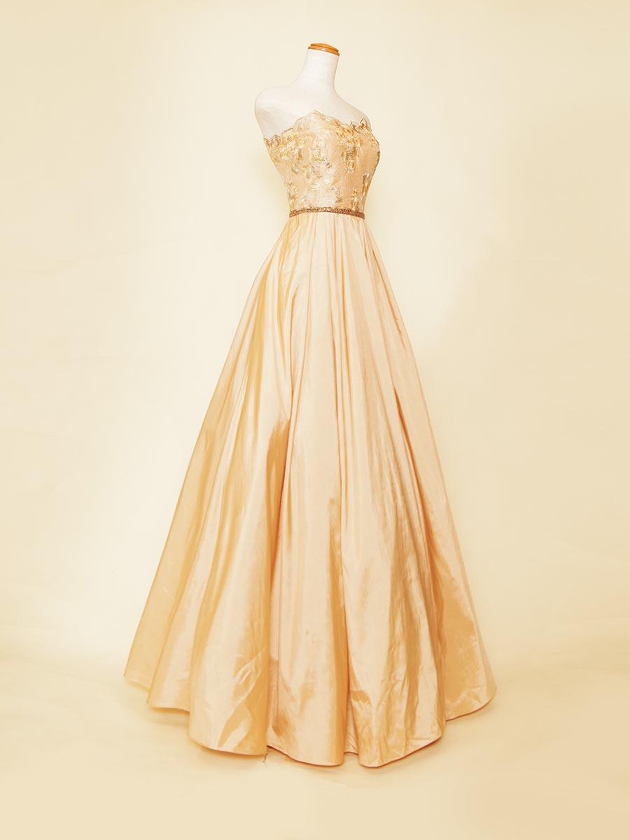 イエローカラーのタフタ生地とゴールド装飾を馴染ませた肌なじみの良いステージロングドレス