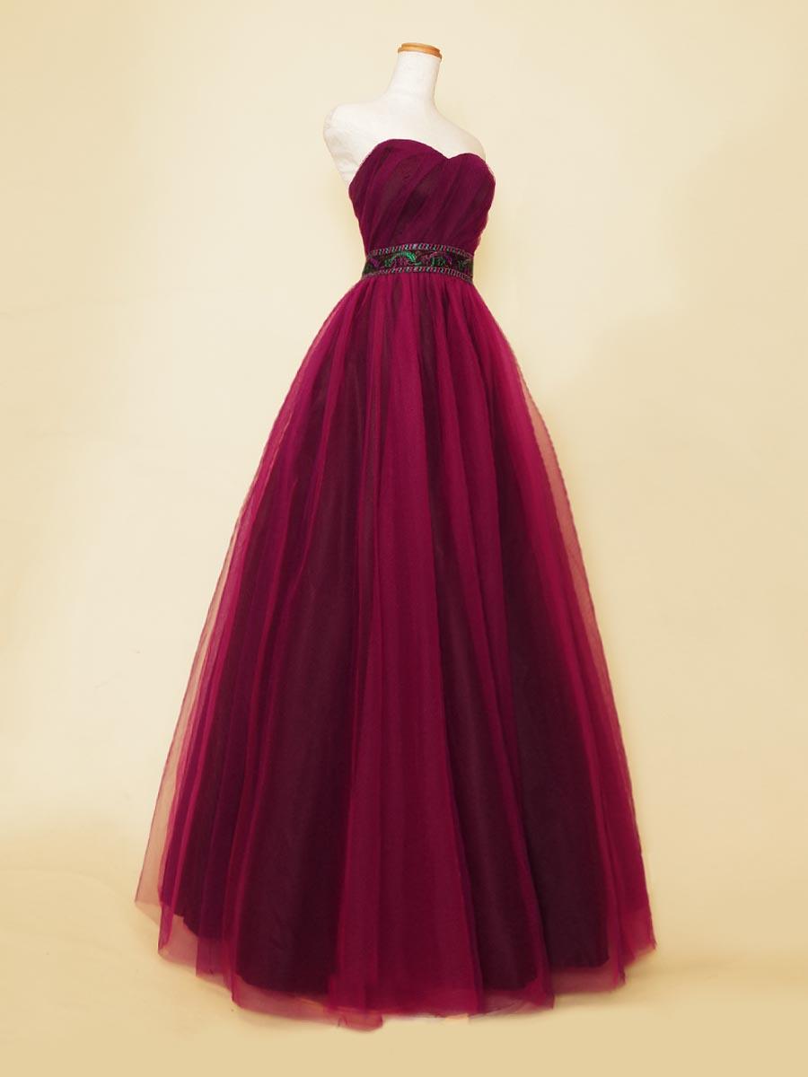 ディープワインパープルカラーのチュール生地で仕上げたエスニックスタイルのウエストベルトが特徴の演奏会ロングドレス