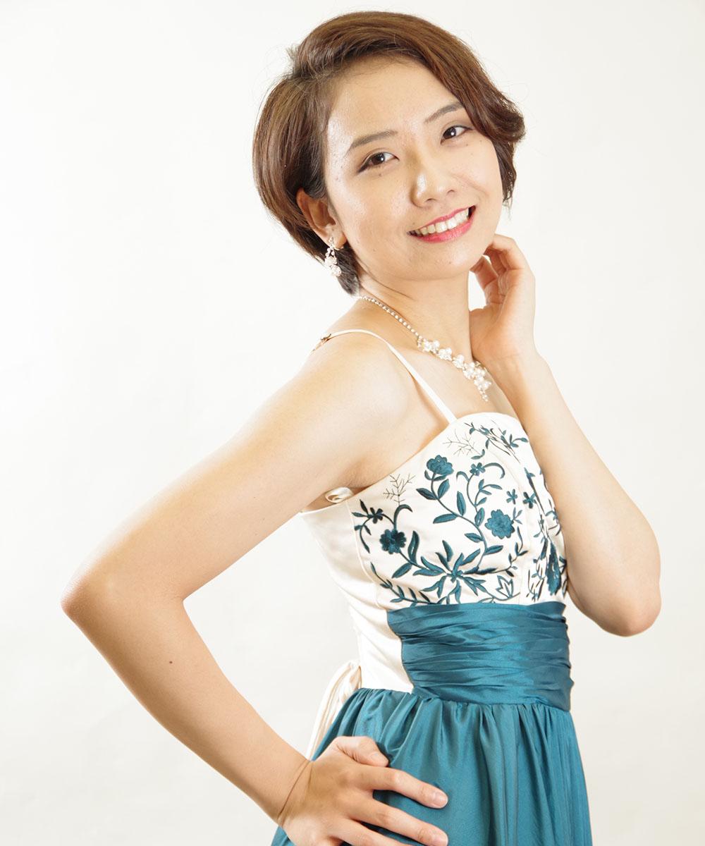 ピアニストのお客様のエメラルドグリーンのドレスを着用した宣材写真