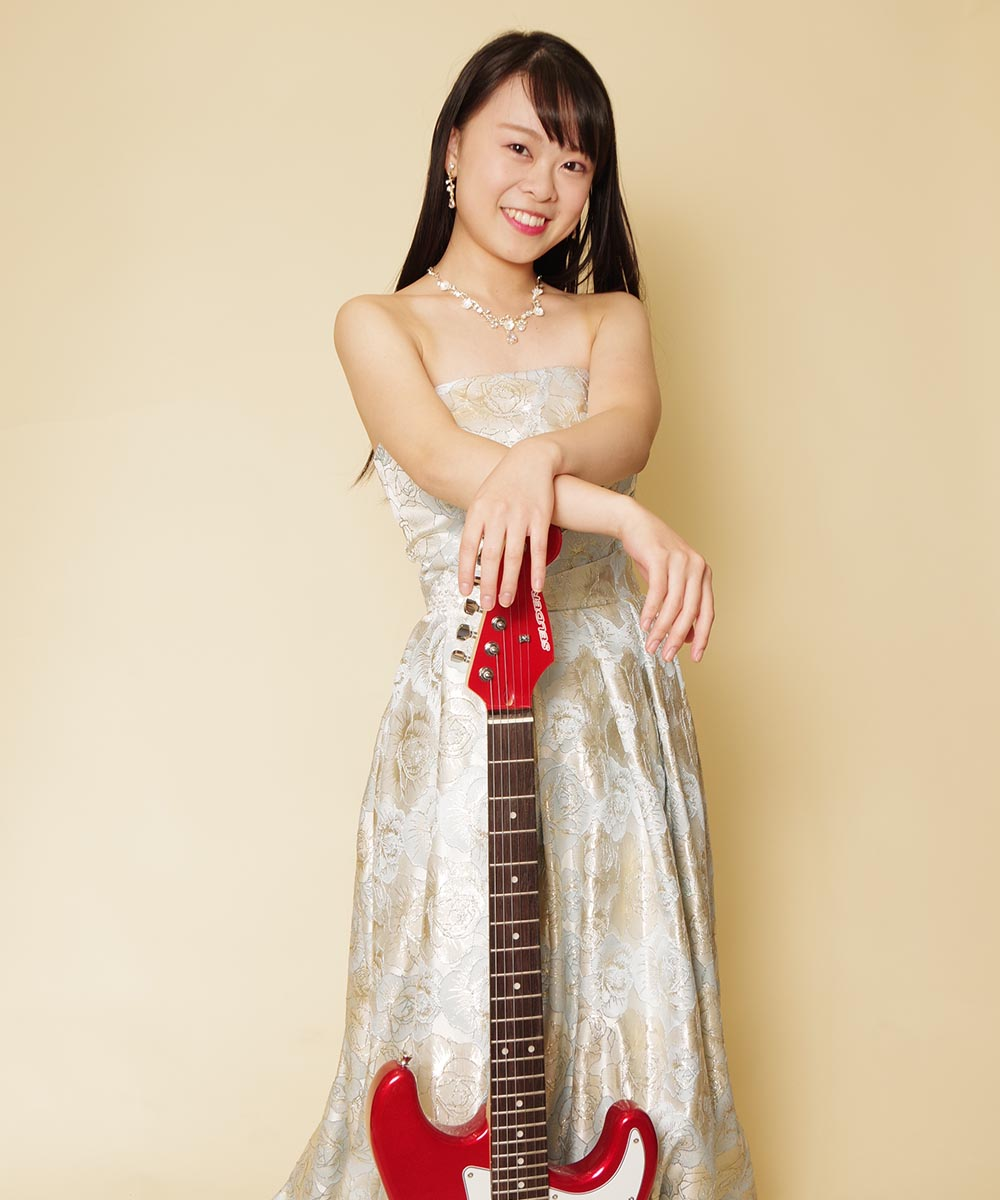 赤いエレキギターを持ってスカイブルーのジャカードドレスを着たプロフィール写真