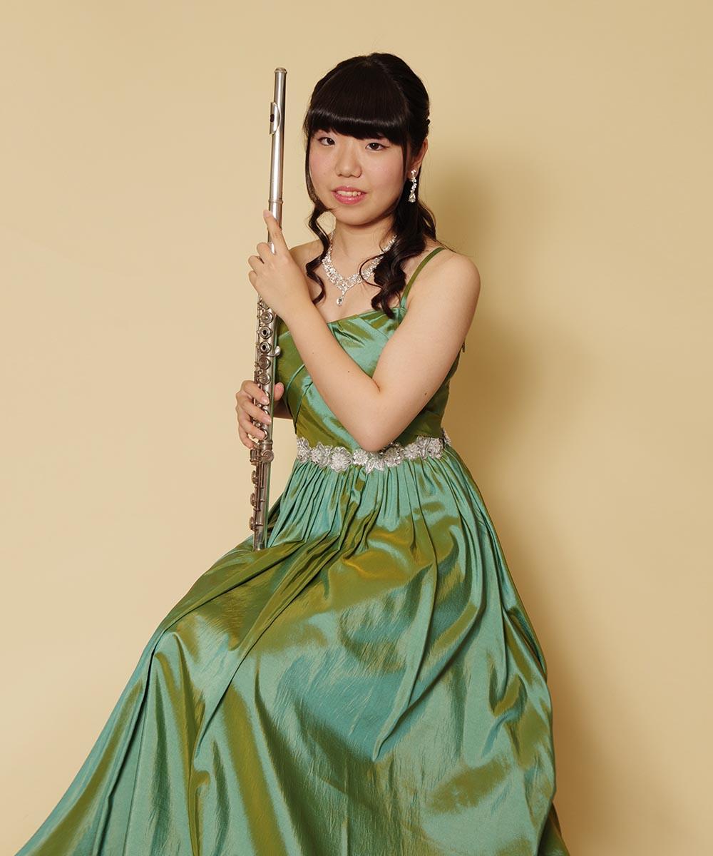 幻想的な光を放つタフタ生地のグリーンカラードレスを着用されてのフルート奏者様の宣材写真