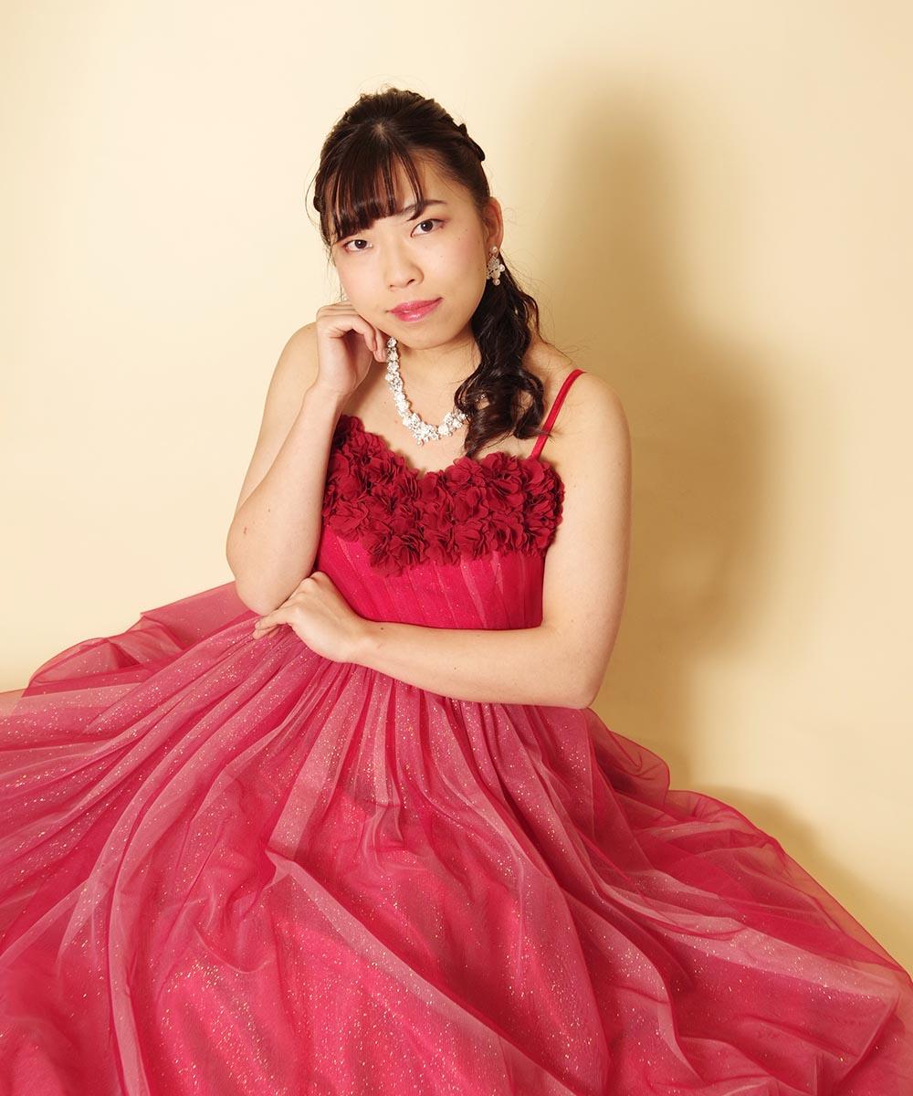 胸元フラワーのキラキラレッドドレスを身にまとった宣材写真