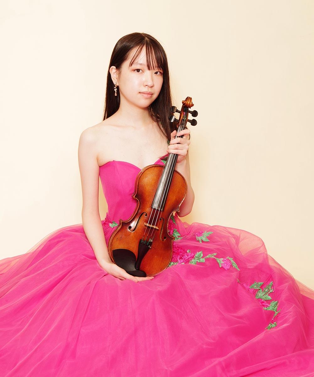 ショッキングピンクのキュートなボリュームドレスを着用されたバイオリニストのお客様の宣材写真