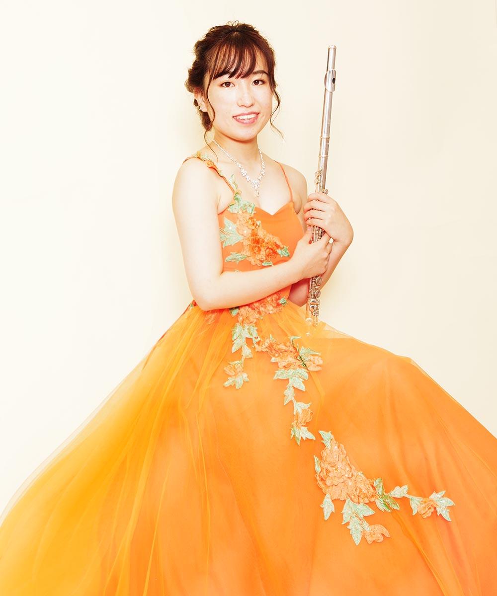 元気なオレンジカラーのボリュームステージドレスを着られたフルート奏者さまの宣材写真
